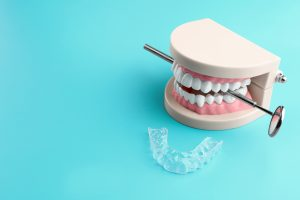 Artificial jaw, dental mirror and occlusal splint on color background