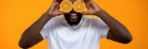 Joyful Afro-American man closing eyes with half of oranges, vitamins for health